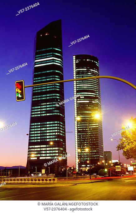 Three colors traffic light and Four Towers, night view. Paseo de la Castellana, Madrid, Spain
