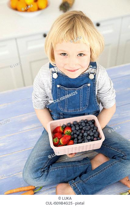 Portrait of cute girl holding punnet of blueberries and strawberries on kitchen counter
