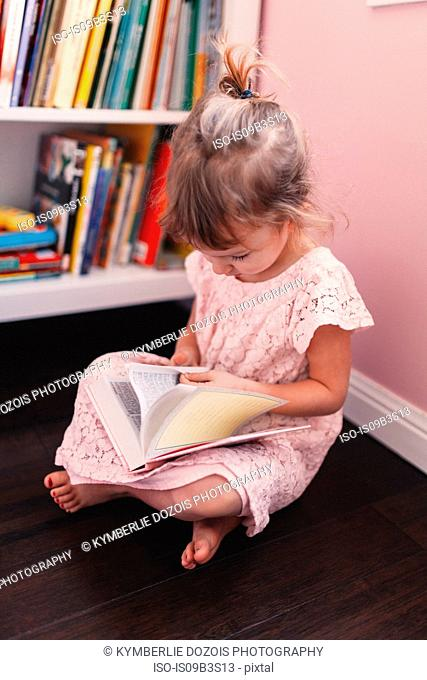 Girl sitting on playroom floor reading book