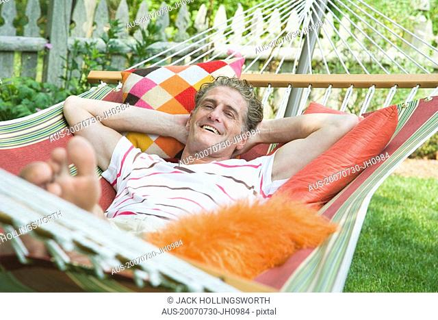 Portrait of a mature man lying in a hammock and smiling