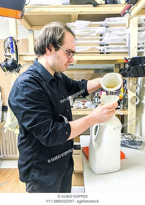 Tilburg, Netherlands. Analog photographic artist pouring his used before chemicals back into a plastic bottle