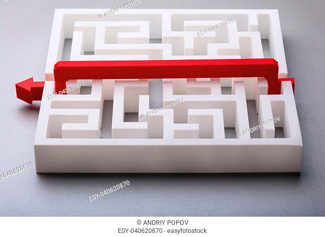 Red Arrow Crossing Over White Labyrinth On Gray Background