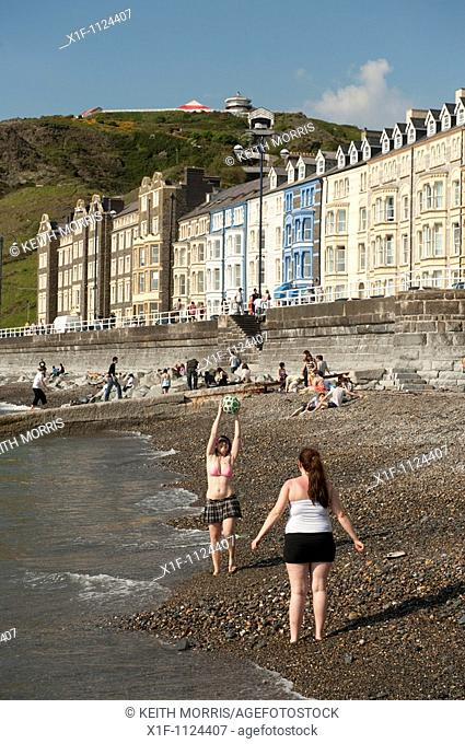 Summer afternoon - students relaxing after their exams and playing on Aberystwyth beach, Cardigan Bay, West Wales, UK