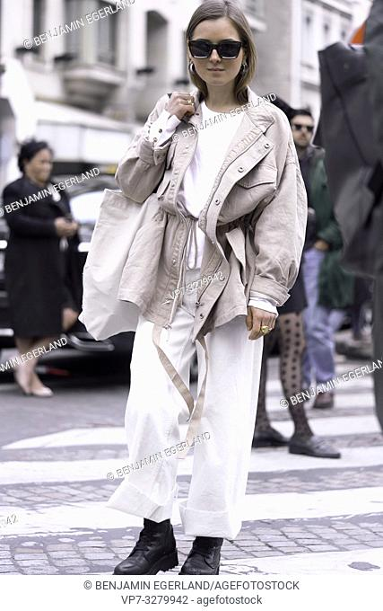 fashionable woman crossing road at crosswalk during paris fashion week, in Paris, France