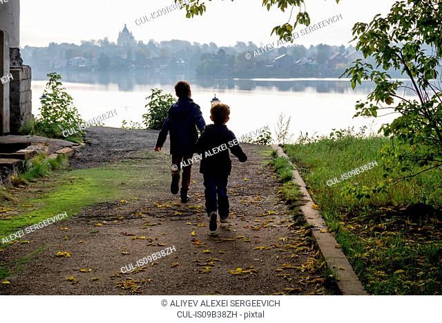 Rear view of two young brothers running toward riverside, Ural, Russia