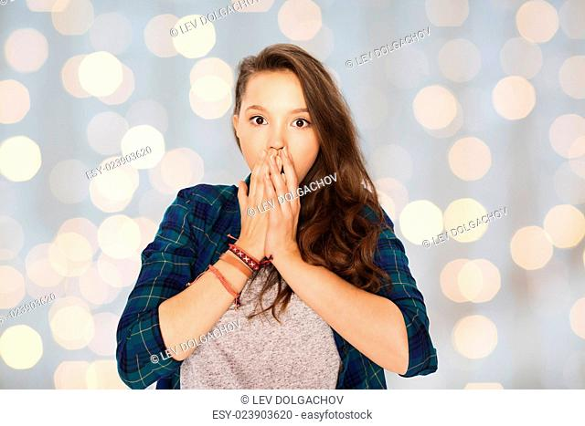 people, emotion, expression and teens concept - scared teenage girl over holidays lights background