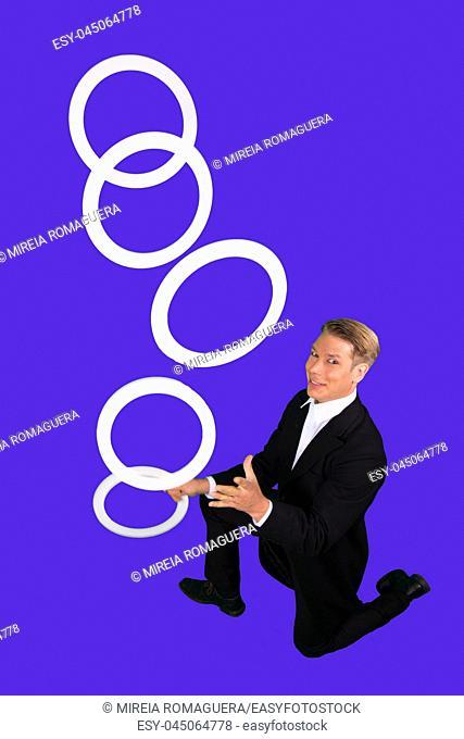 Elegant man juggling with five juggling rings