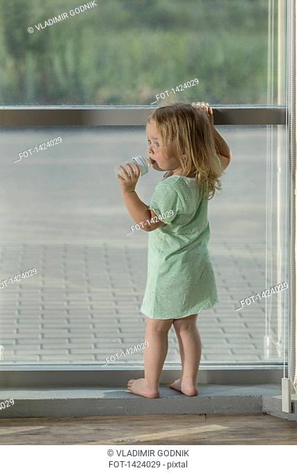 Rear view of girl drinking water while standing by window