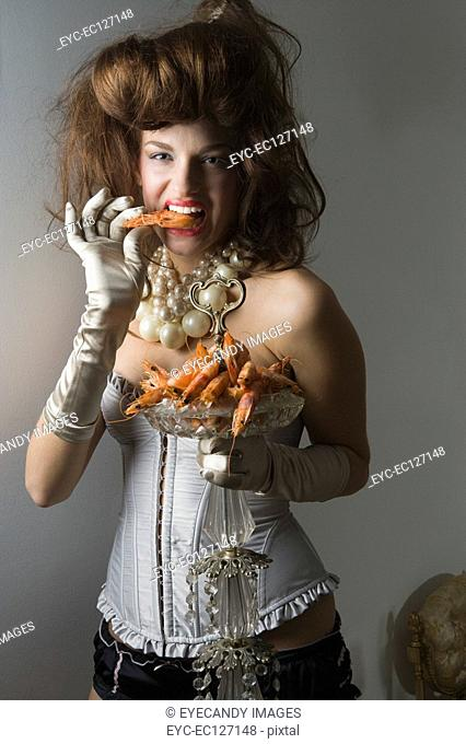 Portrait of woman in corset holding plateful of prawns