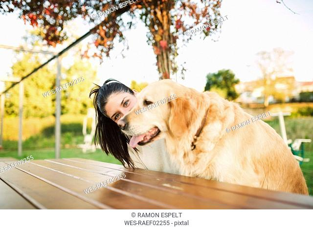 Portrait of young woman with her Golden retriever dog resting in a park