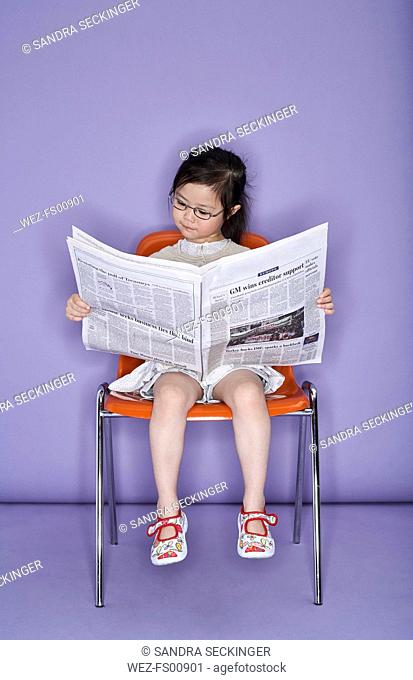 Portrait of little girl sitting on chair with newspaper