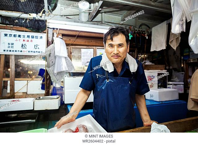 A traditional fresh fish market in Tokyo. A man in a blue apron standing behind the counter of his stall
