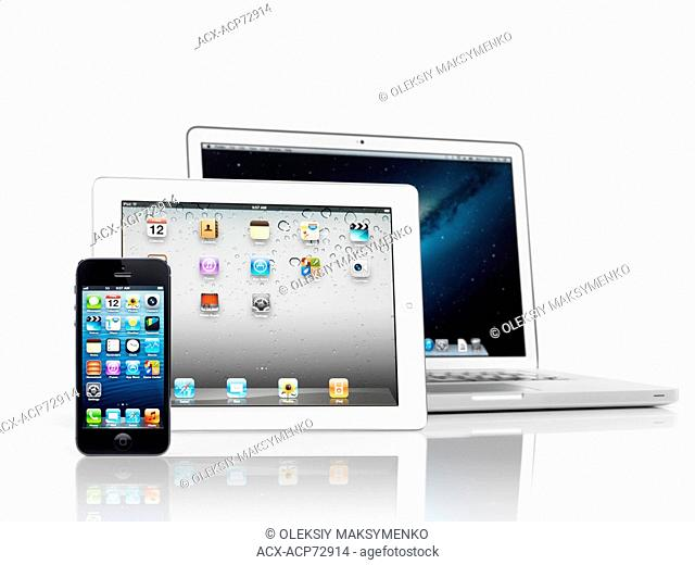 Electronics still life of three Apple devices, iPhone, iPad and Macbook Pro, smartphone, tablet and laptop computer, isolated on white background