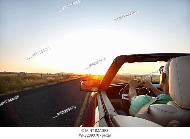 A senior Hispanic man at the wheel of his convertible sports car at sunset in eastern Washington State, USA