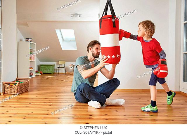 Father holding punchbag for son