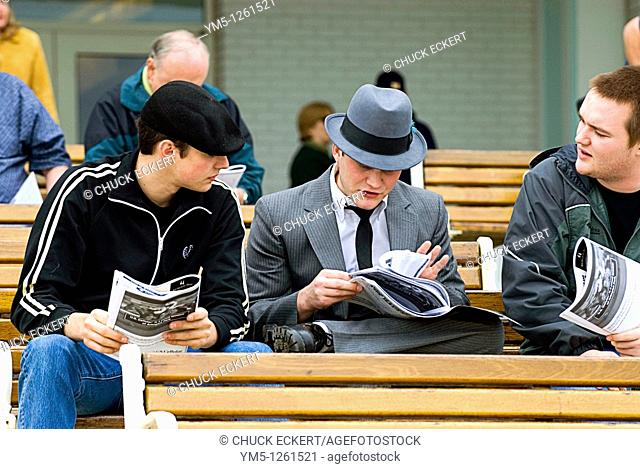 Three young horse racing fans discussing strategy for next race