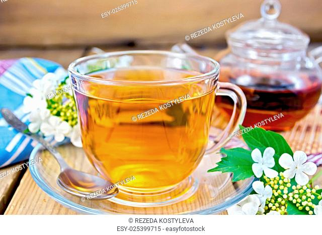 Herbal tea viburnum flowers in a glass cup and teapot, spoon, fresh flowers viburnum, napkin on a wooden boards background