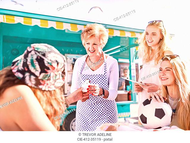 Senior female business owner serving ice cream to young women outside sunny food cart