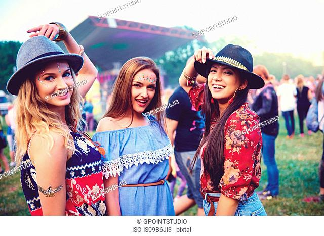 Portrait of three young female friends in trilbies at festival