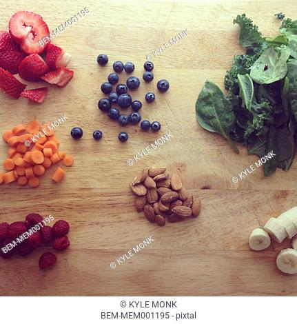 Piles of fruit, nuts and greens on wooden board