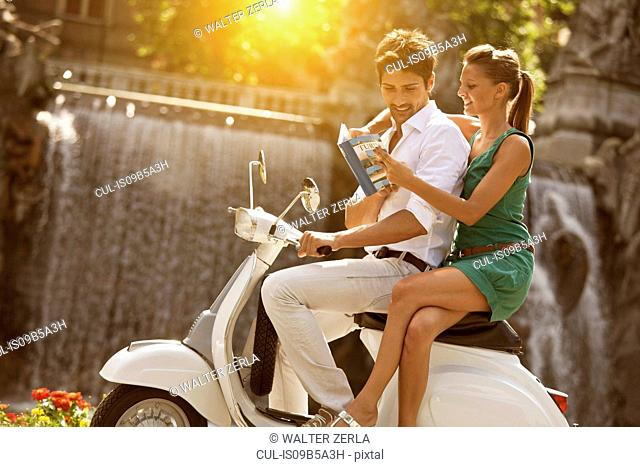 Young couple sitting on scooter, looking at guidebook, Turin, Piedmont, Italy
