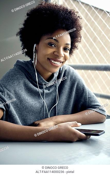 Young woman using listening to earphones, portrait