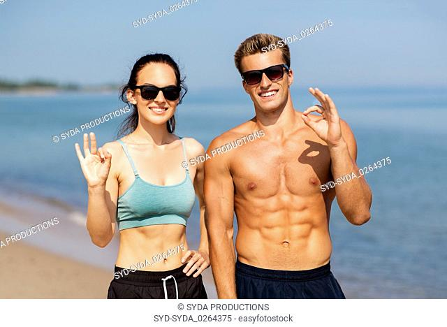 couple of athletes in shades on beach showing ok