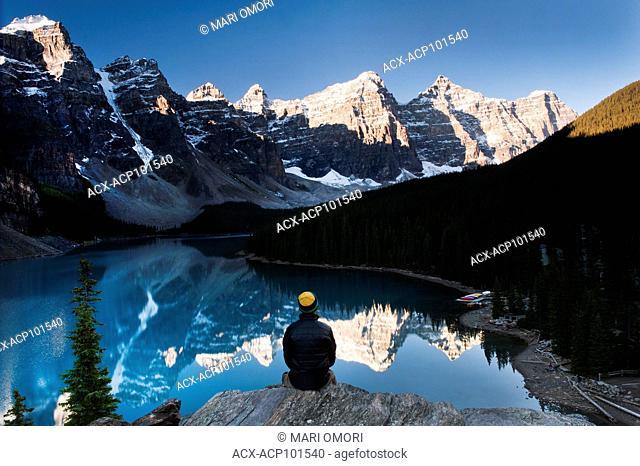 A visitor enjoys the sunrise at Moraine Lake in Banff National Park. Model Release signed