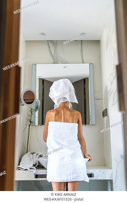 Woman wrapped in towels looking in bathroom mirror