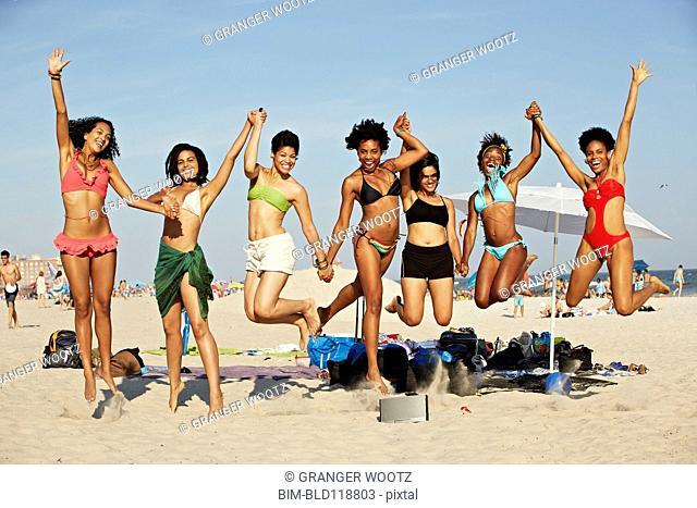 Women jumping for joy on beach