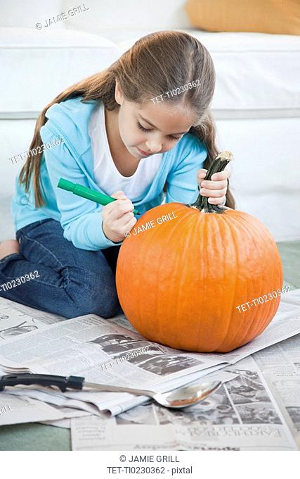 Young girl drawing on pumpkin