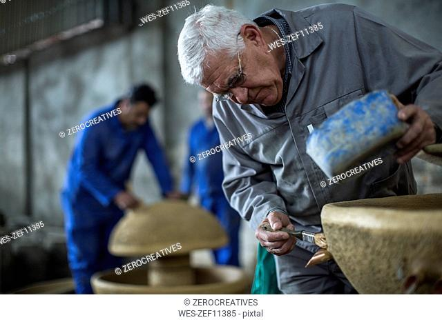 Man working on ceramics in industrial pot factory