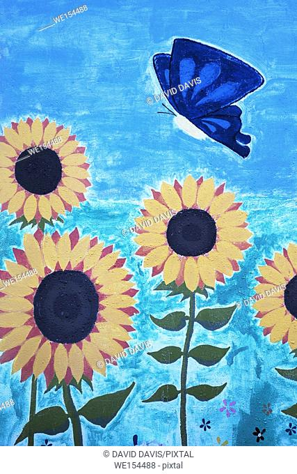 Beautiful outdoor mural of sunflowers and a butterfly