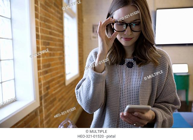 Businesswoman with eyeglasses texting with cell phone in conference room