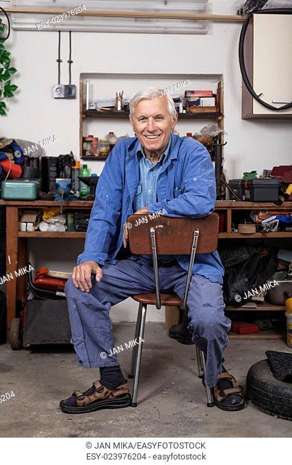 Portrait of happy senior worker sitting in his workshop