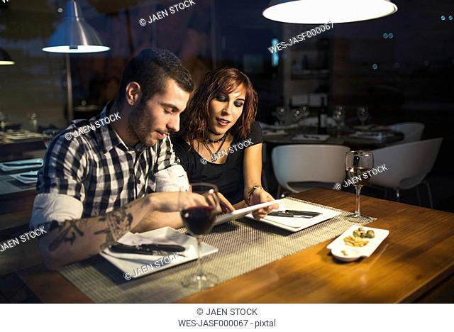 Young couple with digital tablet in a restaurant at night