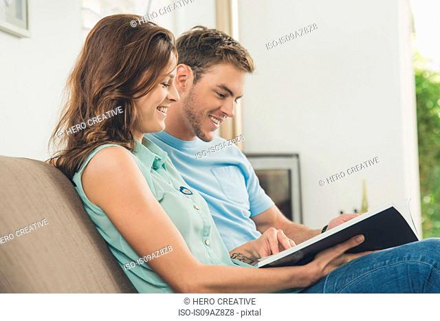 Couple on sofa looking at book smiling