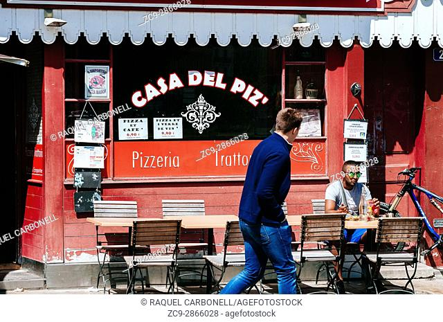 Young man eating at Pizzeria restaurant terrace. Nantes, Brittany, France