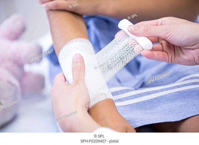Girl having bandage applied to arm