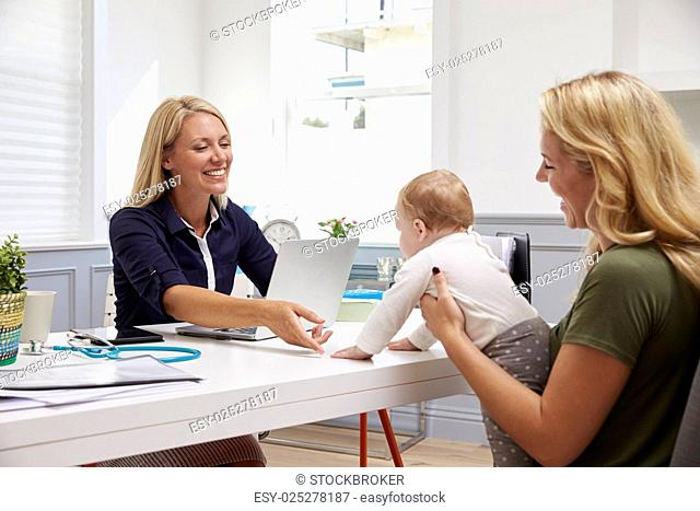 Mother And Baby Meeting With Female Doctor In Office