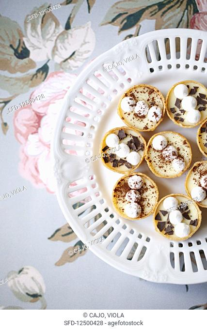 Mini tarts filled with cream, meringue, chocolate chips and cocoa (top view)