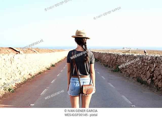 Spain, Menorca, back view of single traveller on county road