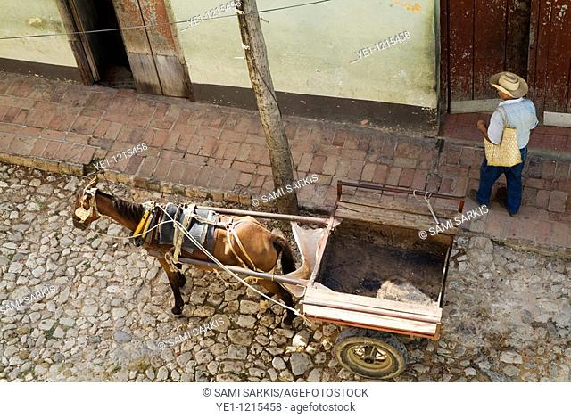 Man walking past a horse and cart parked in a street, Trinidad, Cuba