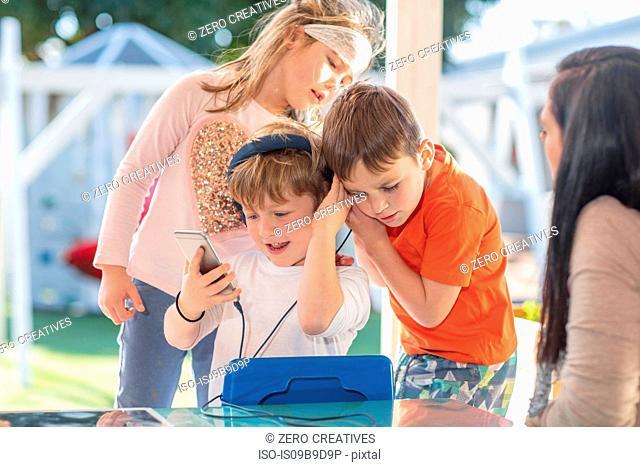 Three young children, using smartphone, listening through headphones