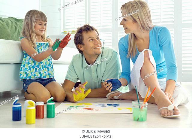 Family finger painting on floor