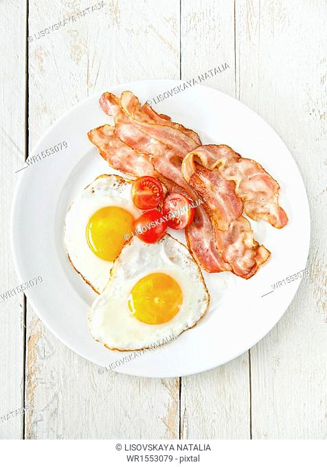 Eggs and bacon with tomato for breakfast