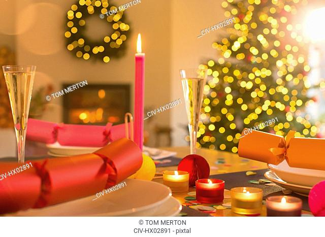 Candles, champagne and Christmas crackers on table
