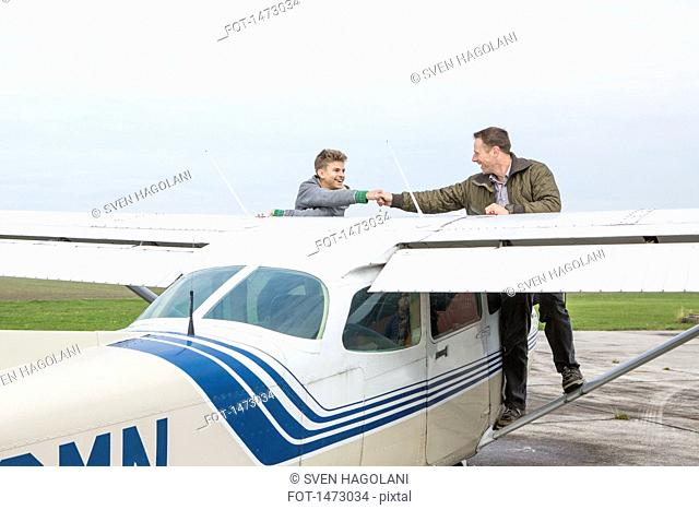 Father and son shaking hands over private airplane