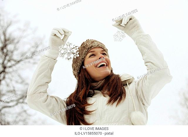 A young woman holding two snowflake decorations