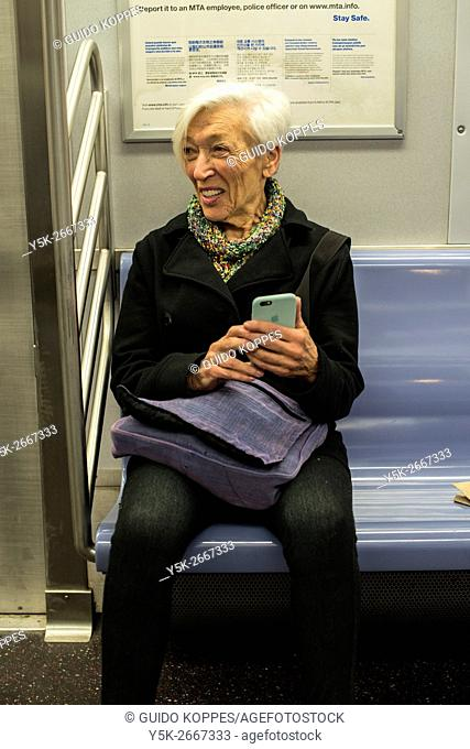 New York City, USA. Senior adult woman commuting with happyness and joy using the New York Subway into Manhattan